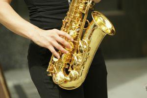 bildet viser noen hender som spiller på en saksofon