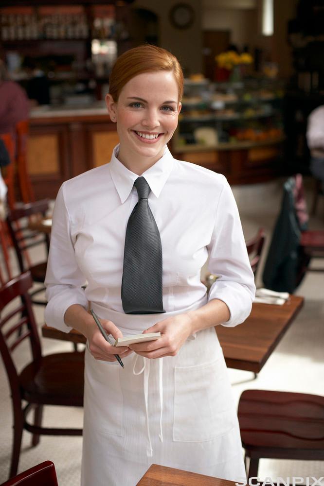 En smilende servitør i uniform står ved et bord. Foto.