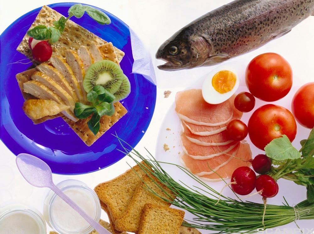 Ulike matvarer som er lagt opp på tallerkener. Vi ser blant annet egg, en hel fisk, tomat, skinke og brød.  Foto.