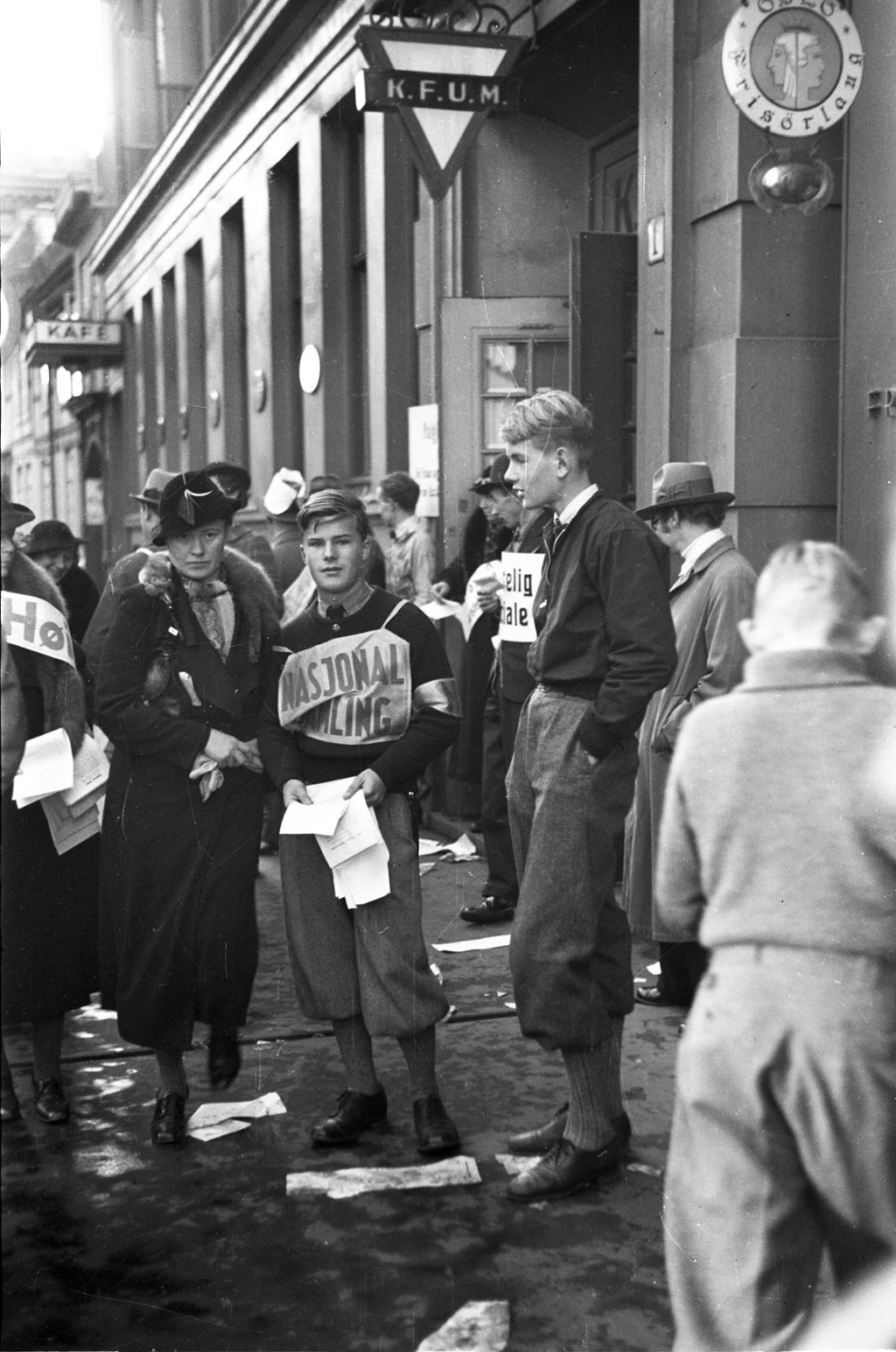 Valgtorg med en ung gutt med NS-banner. Foto.