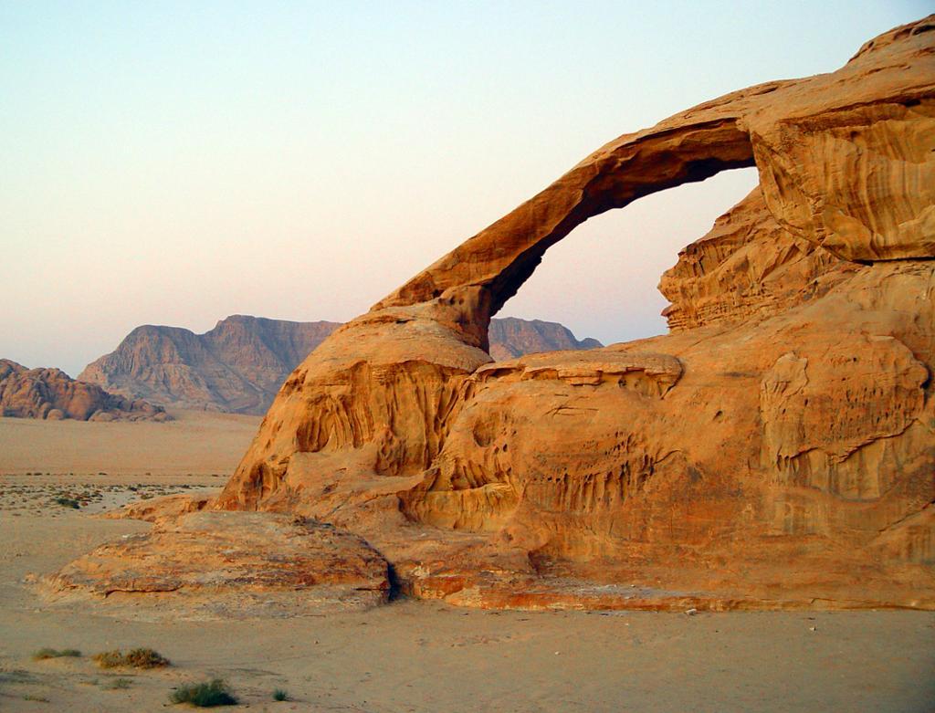 Bilde av et fjell som har forvitret slik at det har dannet seg et stort hull med en smal, bueformet stripe fjell over hullet. Foto.