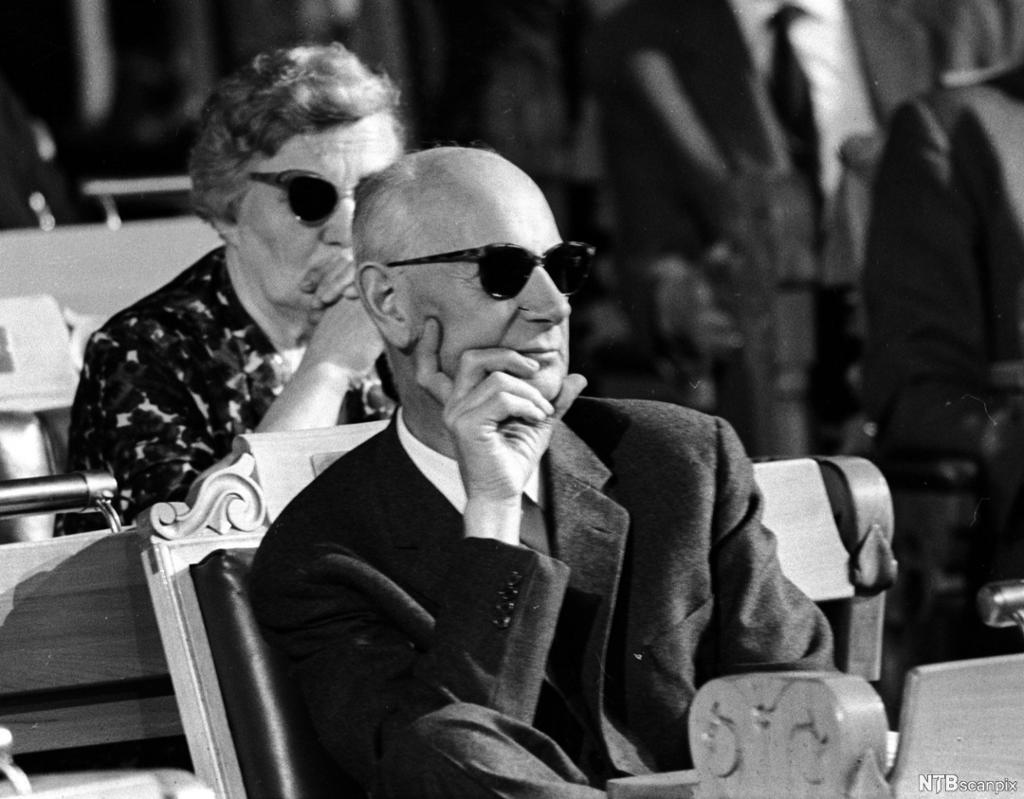 Einar Gerhardsen sitter i Stortingets sal med solbriller på og lytter. Foto.