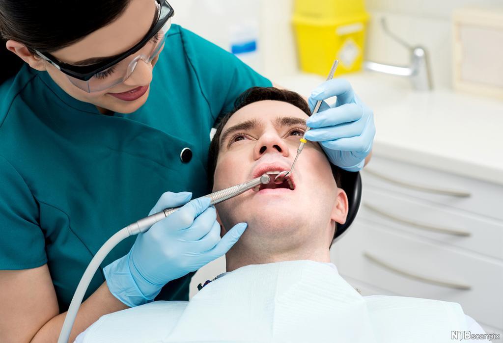 Tannlege behandler pasient. Foto.
