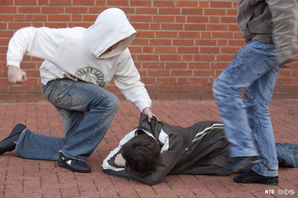 Ein gut ligg på bakken og blir slått og sparka av to andre. Foto.