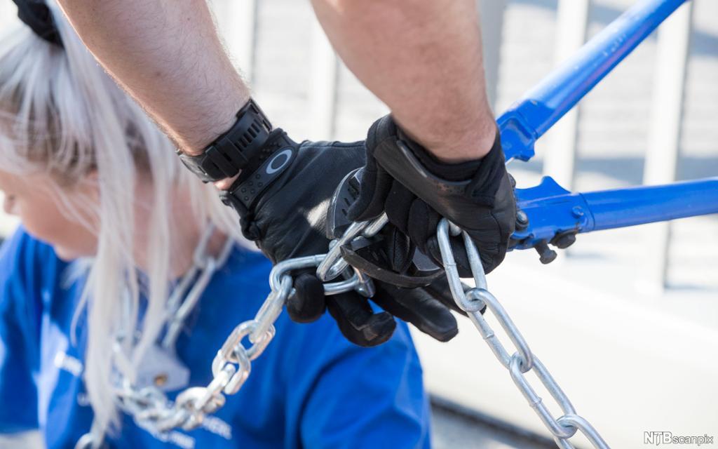 En aksjonist som har lenket seg fast, blir klippet løs med bitetang. Foto.