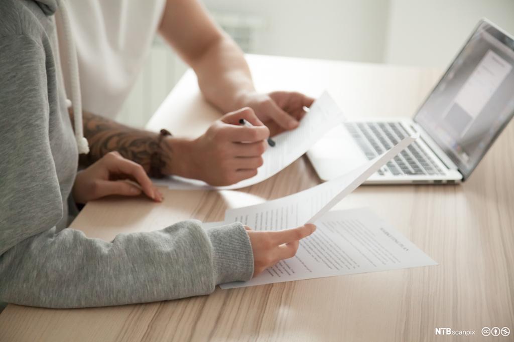 To personer studerer tekst på papir og PC. Foto.