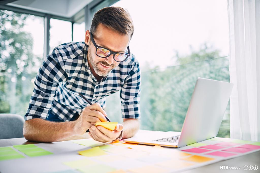 Mann med briller skriver notater på gule lapper. Foto.
