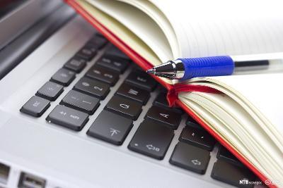 En kulepenn og skrivebok ligger oppå en bærbar datamaskin. Foto.