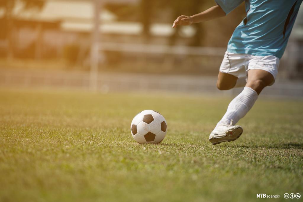 Fotballspiller i ferd med å sparke en ball. Foto.