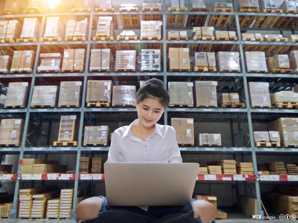 Kvinne skanner strekkoden for å lagre varehusdata. Foto