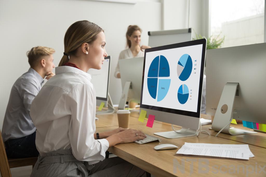 Ung kvinne jobber med statistikkdiagrammer på datamaskin. Foto.