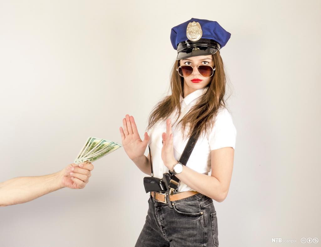 Dame kledd ut som politi som ikke vil motta penger. Foto.