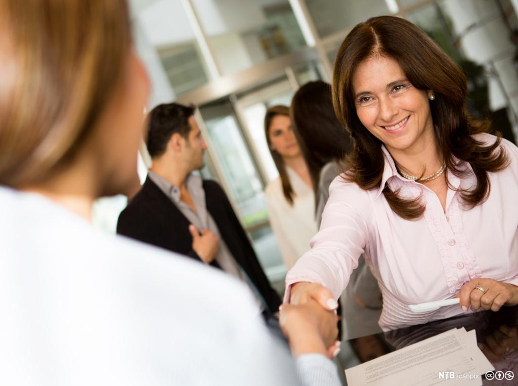 En forretningskvinne sjekker inn på et hotell og smiler. Foto.