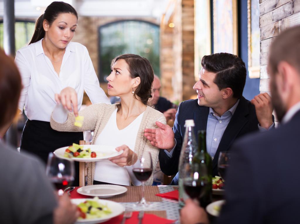 Misfornøyde restaurantgjester klager til servitør. Foto.