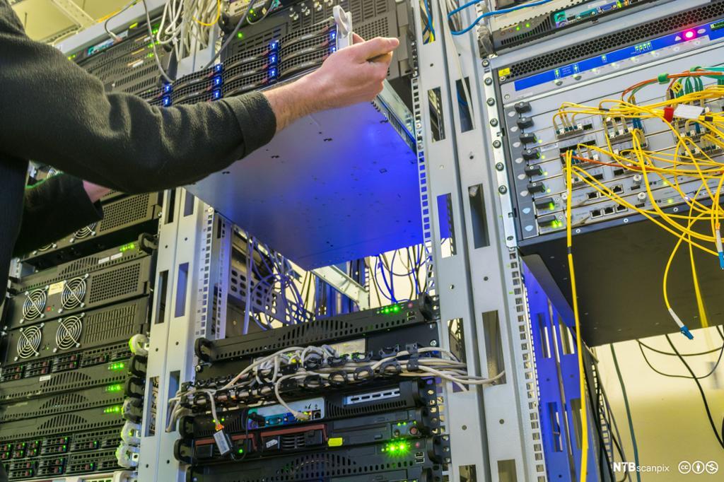 Teknikker monterer en server inn i et rack skap. Foto.