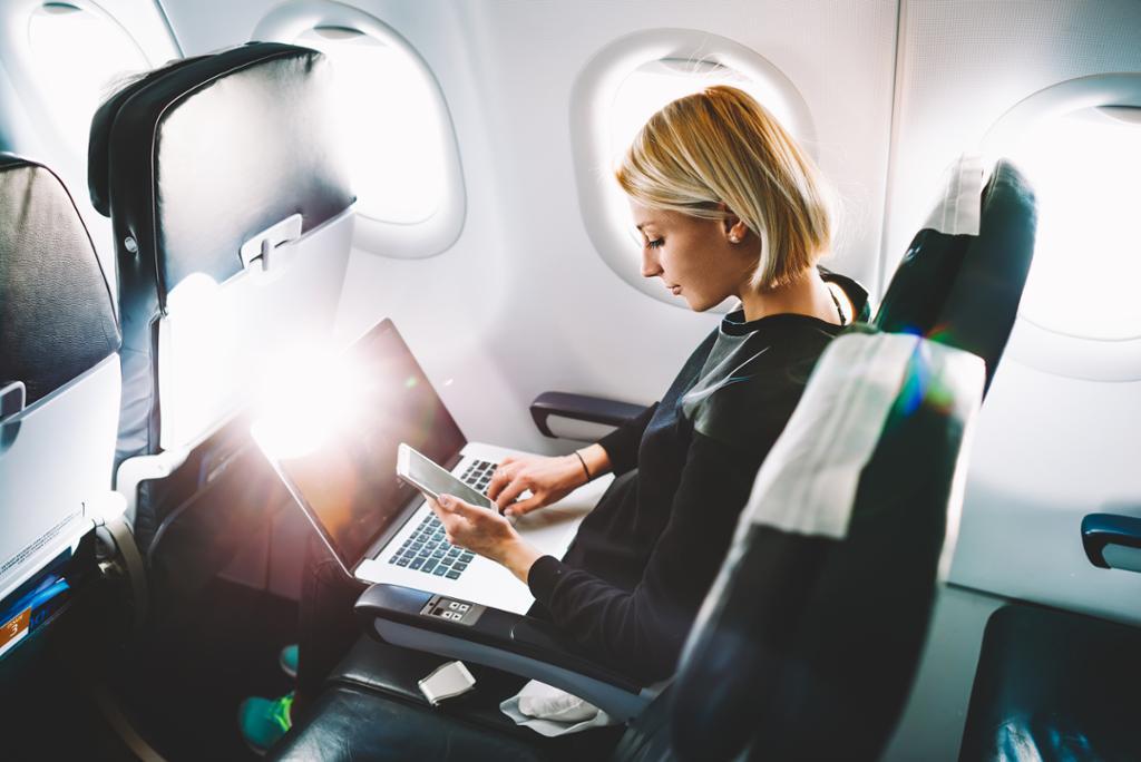 Forretningskvinne deler media fra mobil på bærbar datamaskin under flytur. Foto.