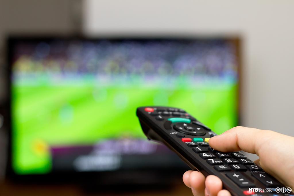 Hånd med TV-kontroll foran sportssending. Bilde.
