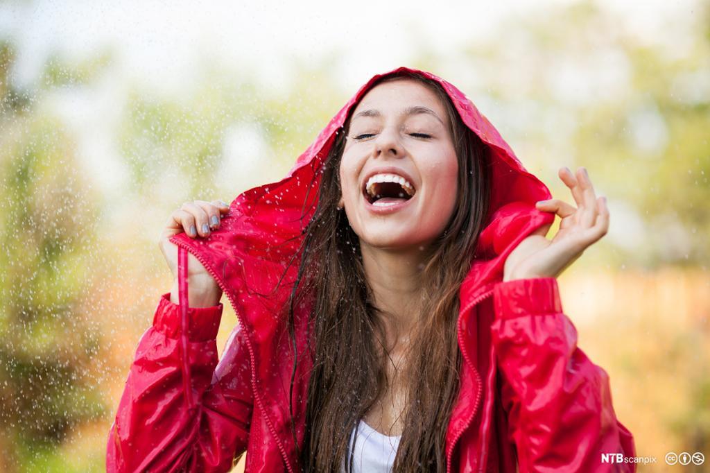 Dame i regnjakke som liker regn. Foto.