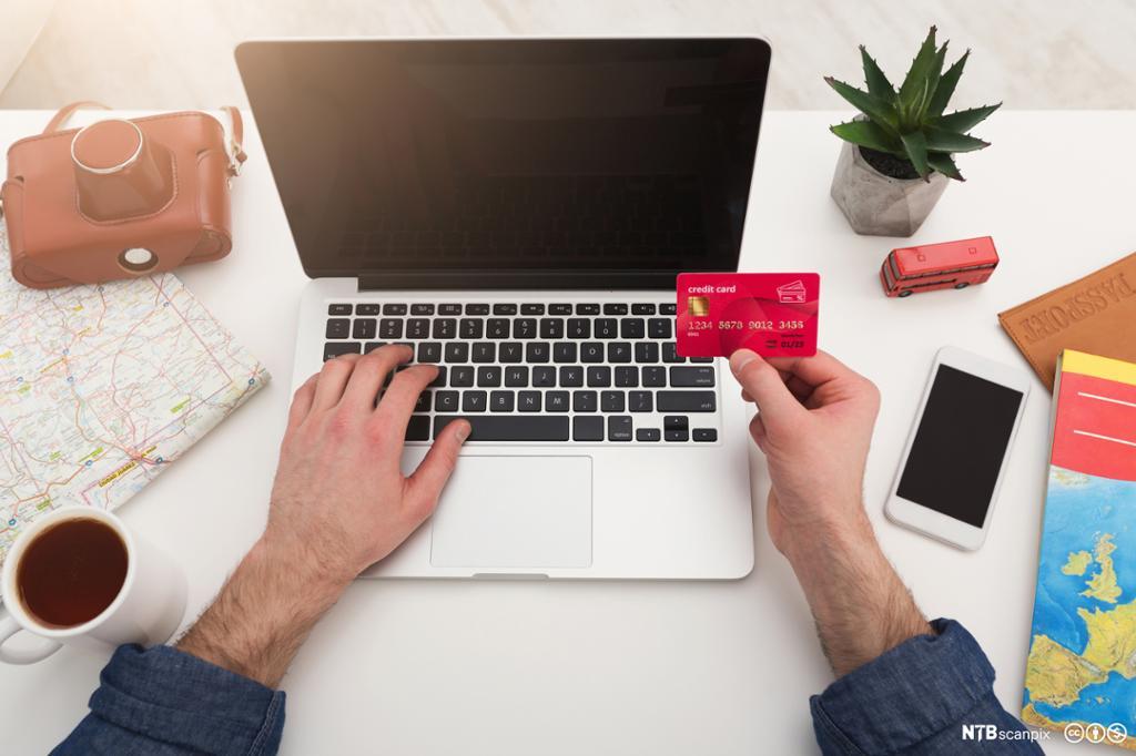 En person handler på nett med et kredittkort. Foto.