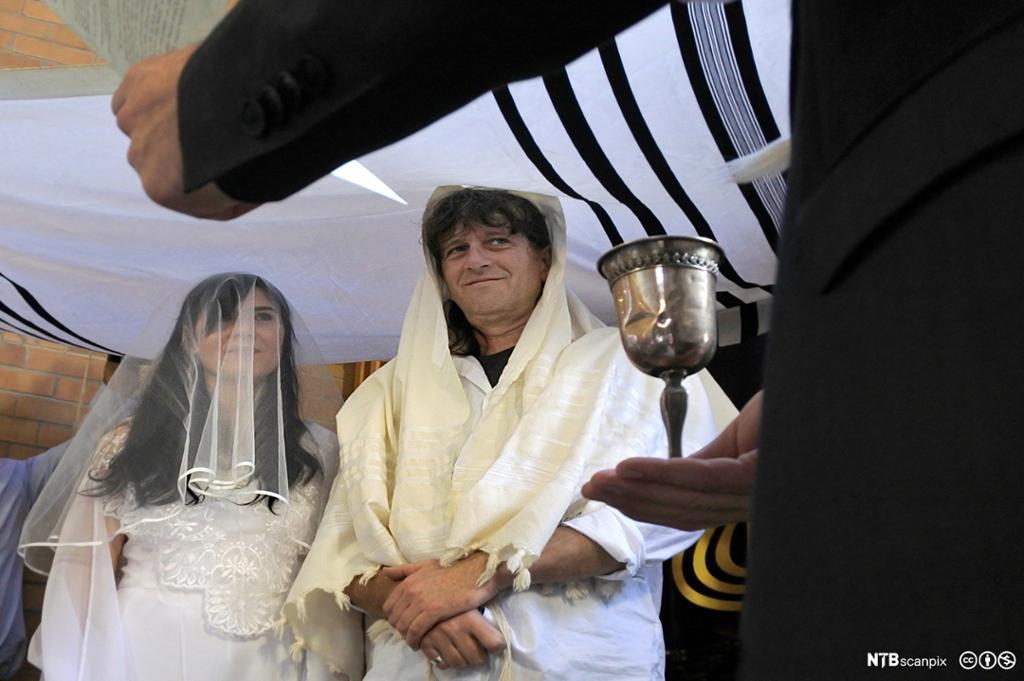 Et jødisk brudepar under en baldakin og en rabbiner som holder opp et glass vin. Foto.
