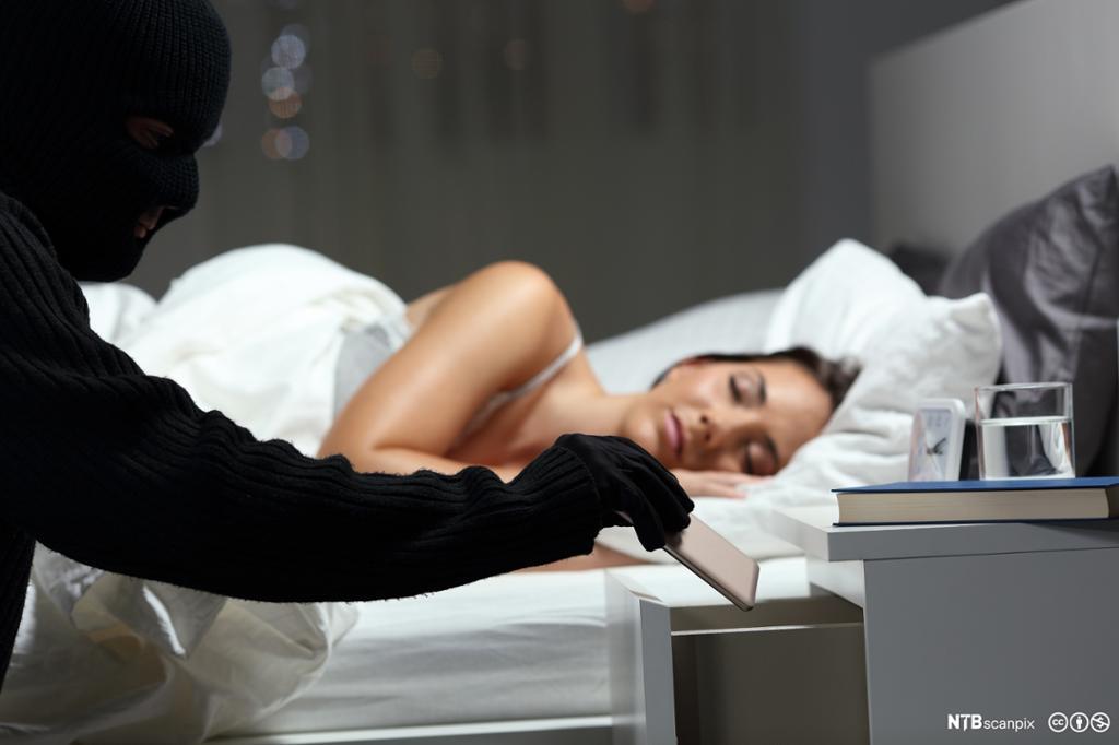 Tyv stjeler fra kvinne som sover. Foto.