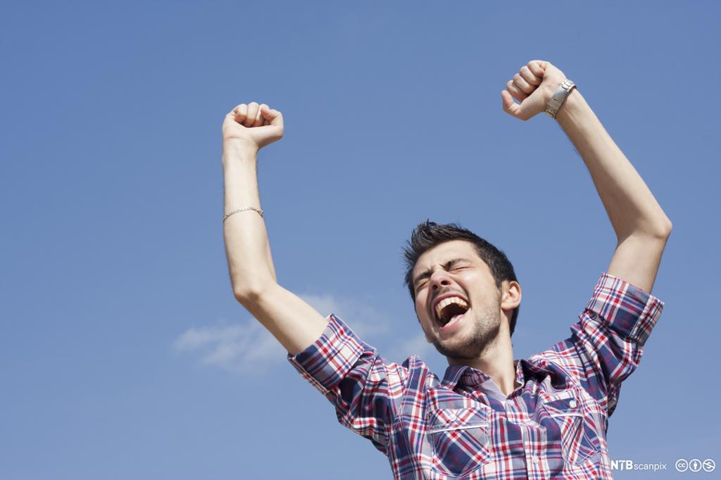 Glad ung mann som løfter hendene i været mot en blå himmel
