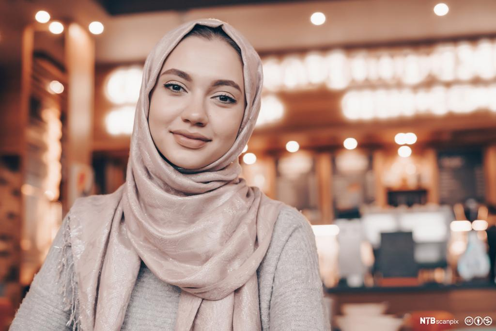 Smilende muslimsk kvinne med hijab. Foto.