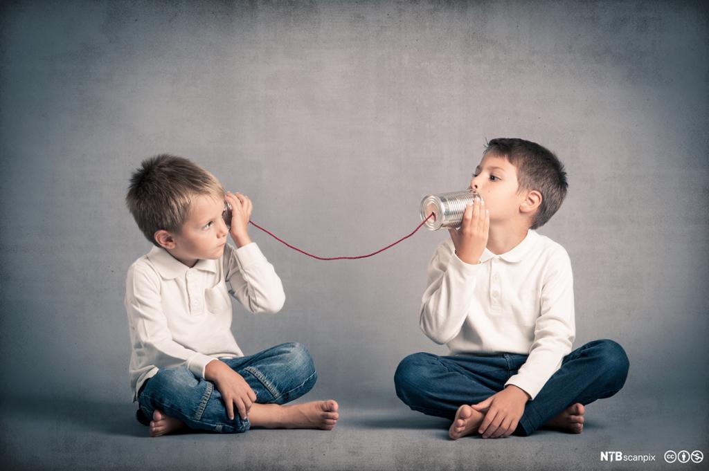 To gutter som snakker i en trådtelefonleke