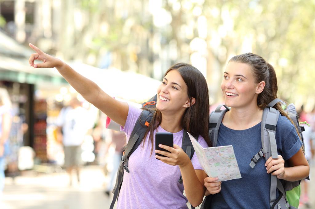 To glade turister gjør sightseeing i en storby. Foto.