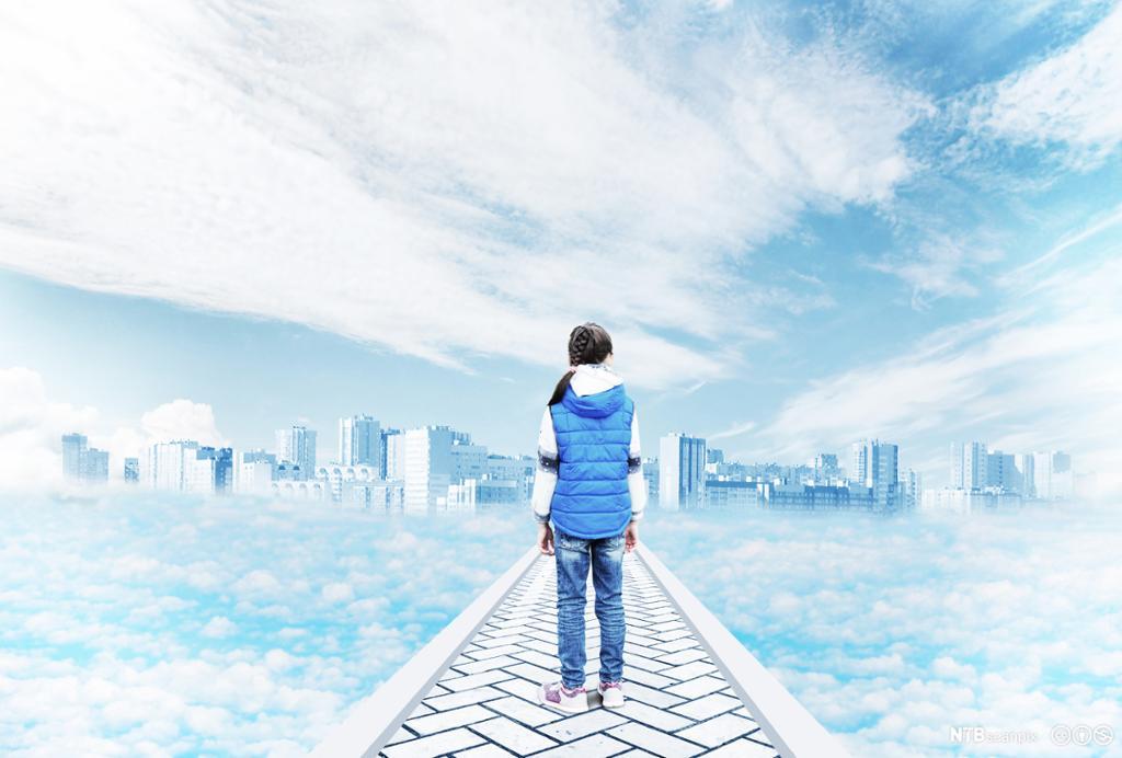 Gutt står på en vei med ryggen til og ser utover en by. Omgitt av skyer. Digitalt bilde.