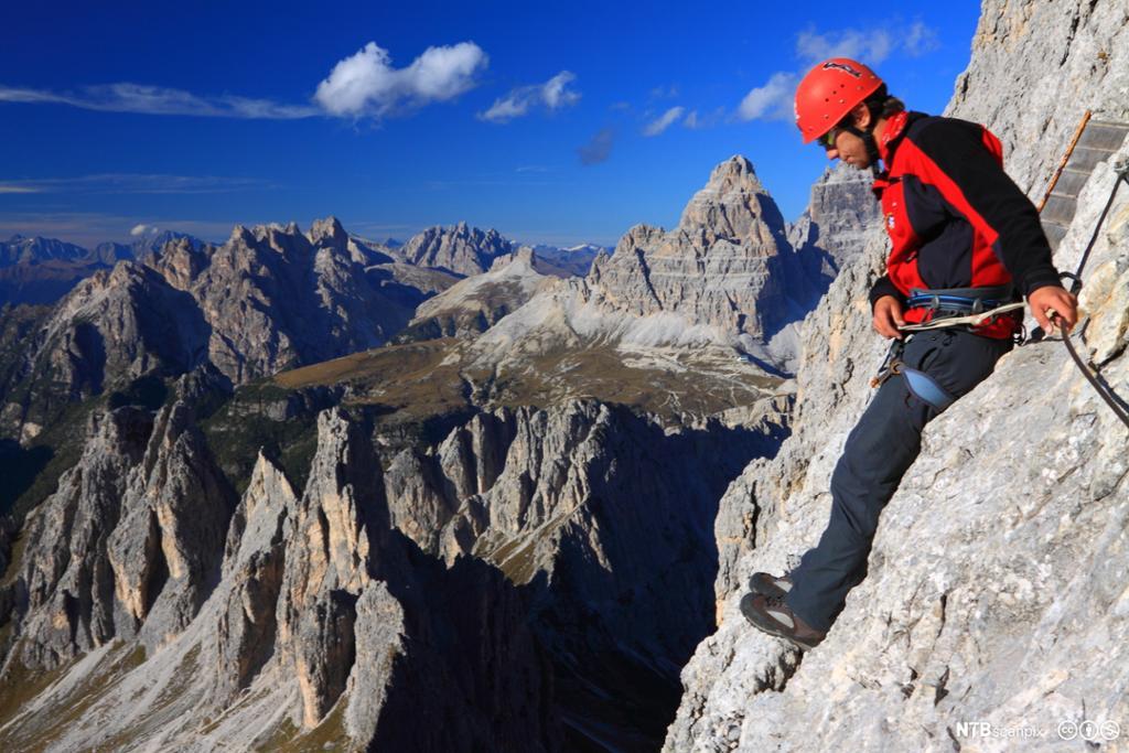En fjellklatrer hviler på en liten hylle. Foto.