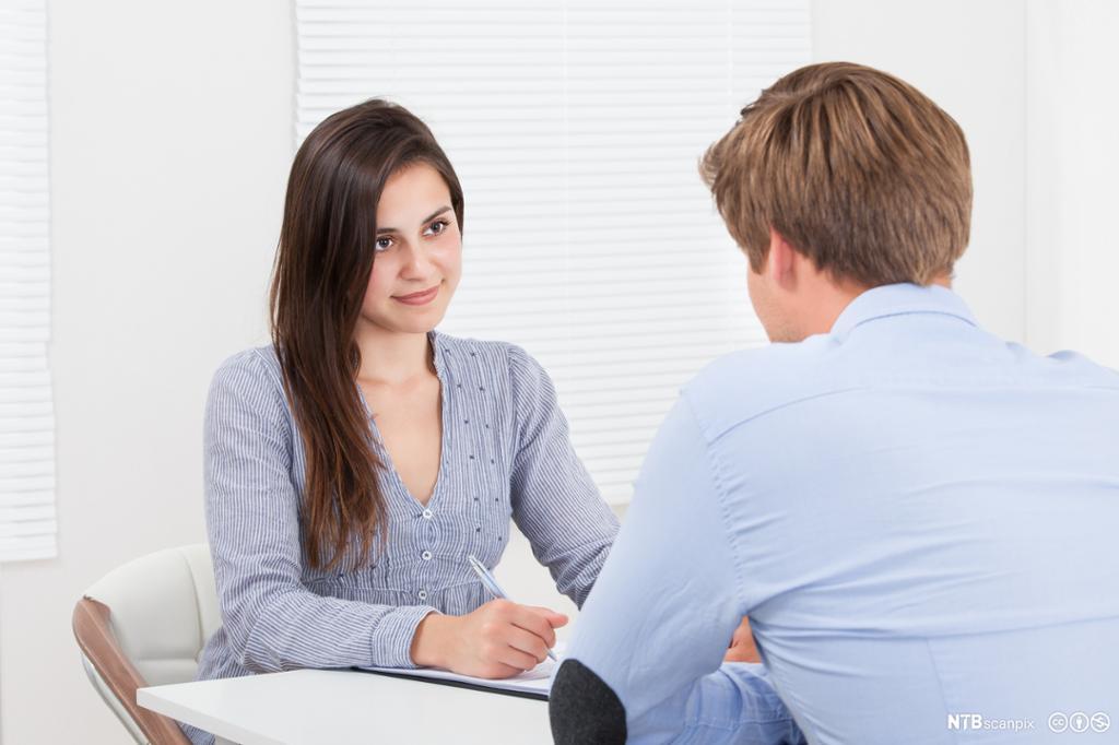 Et fotografi av en kvinne som snakker med en mann.