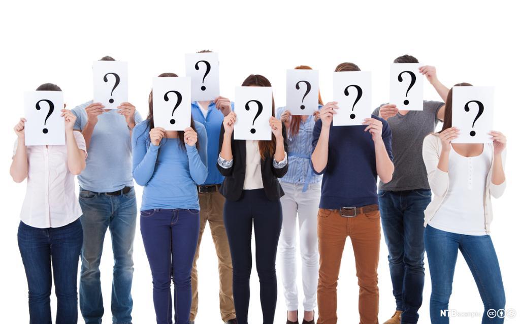 Gruppe mennesker som holder ark med spørsmålstegn foran ansikt. Foto