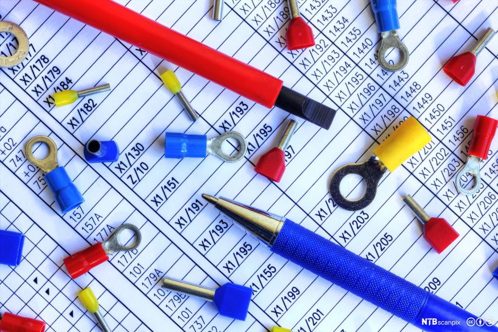 Elektriske komponenter og penner på et skjema. Foto.