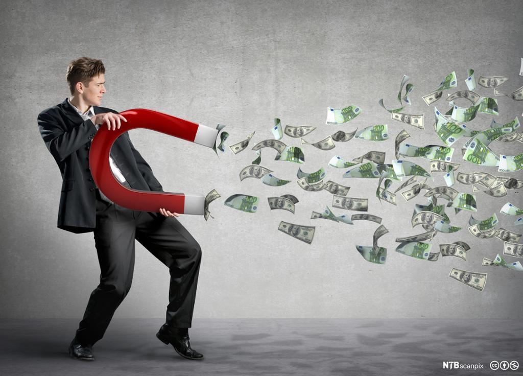 Mann holder en diger magnet som trekker til seg penger. Foto: