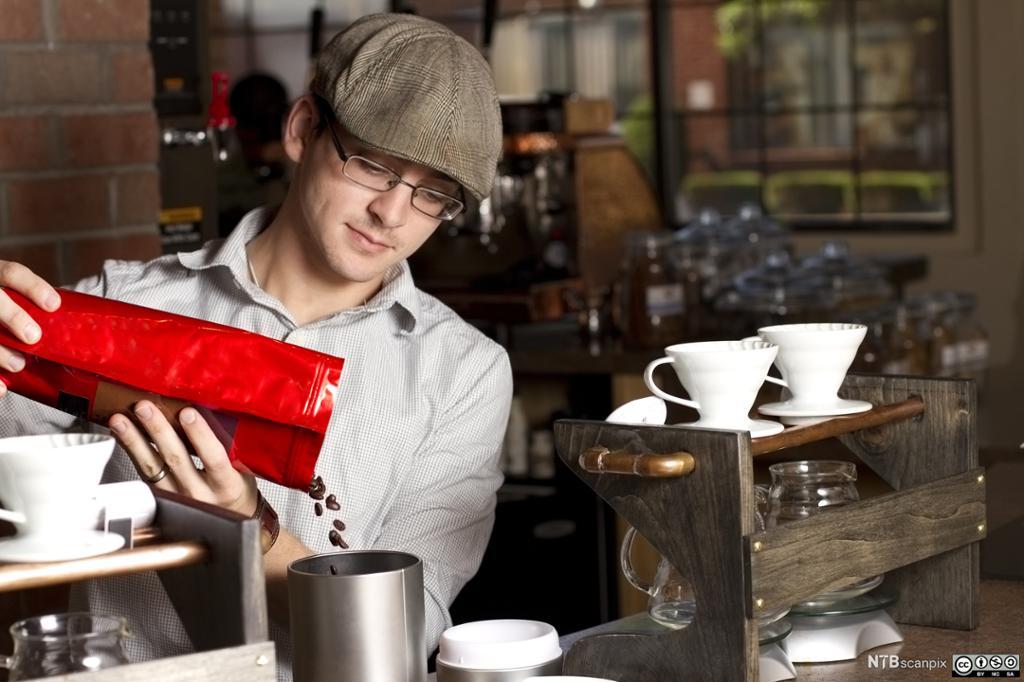 Person heller kaffebønner i en kaffekvern. Foto.