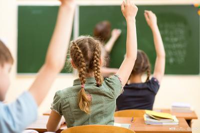 Elever som rekker opp hånda i klasserom. Foto