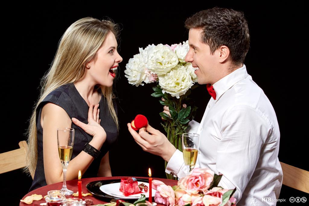 Mann frir til kvinne med ring og blomster. Foto.
