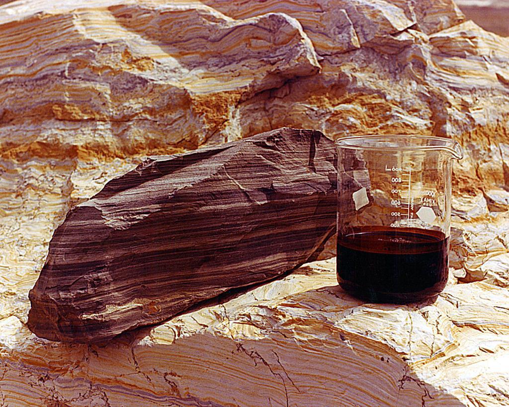 Skiferstein og olje i et beger. Foto.