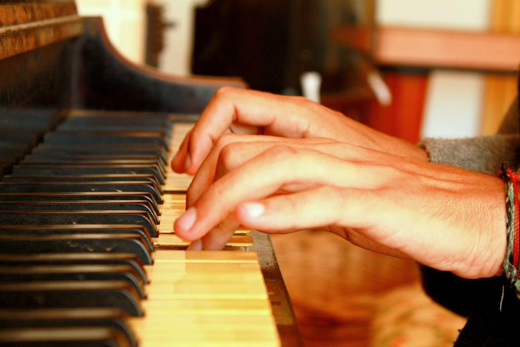 Hender som spiller piano. Foto.