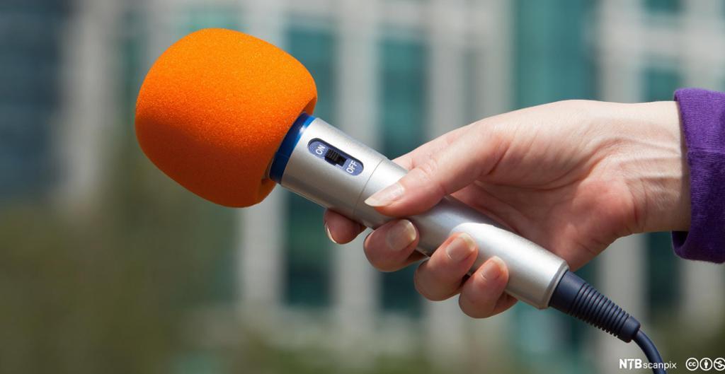 Nærbilde av kvinnehånd som holder en orange mikrofon. Foto.
