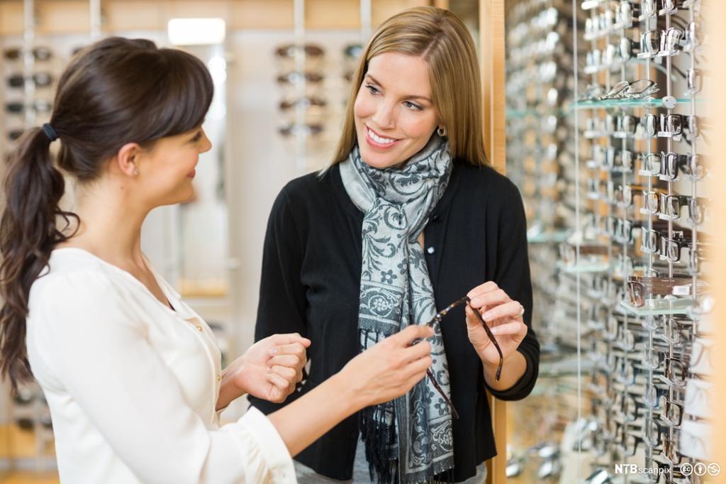Selger viser en dame briller på en brillebutikk