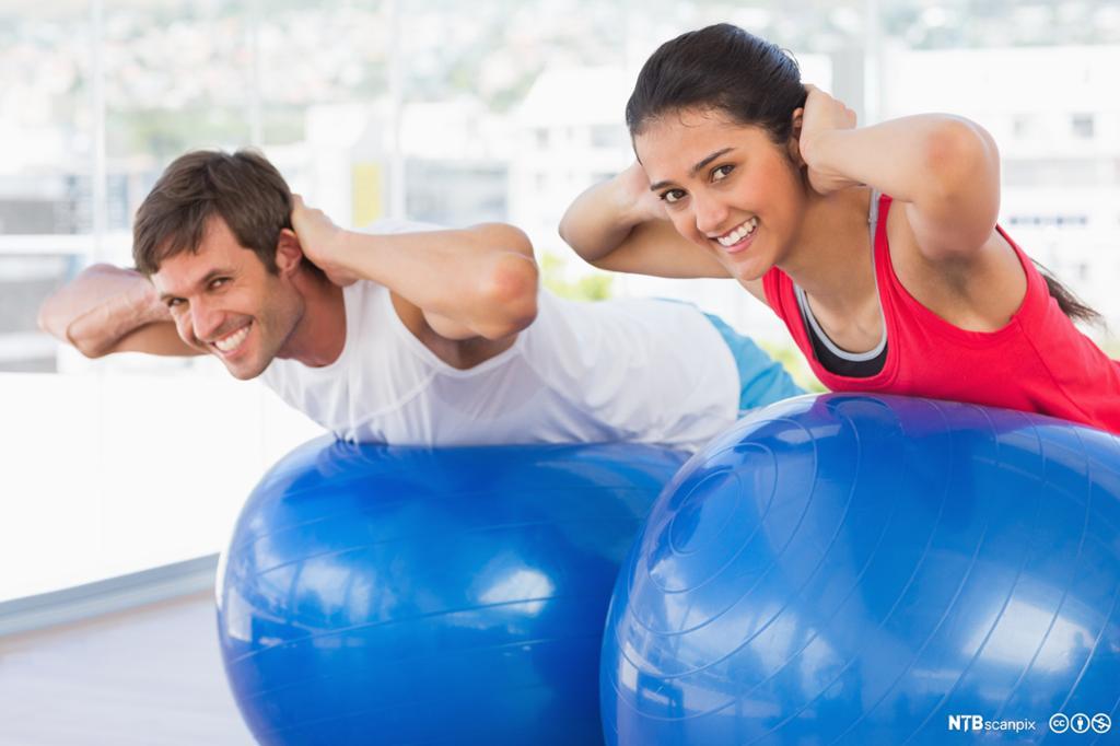 Kvinne og mann trener med fitnessball. Foto.