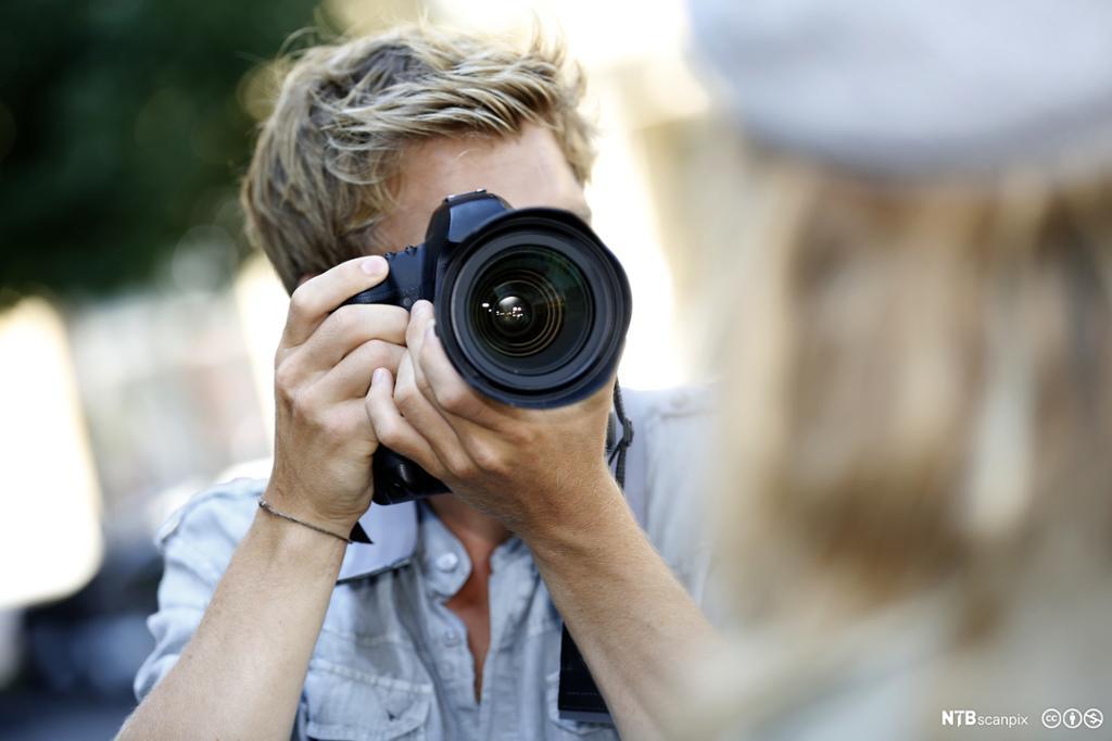 Dame filmar med eit digitalt videokamera. Foto.