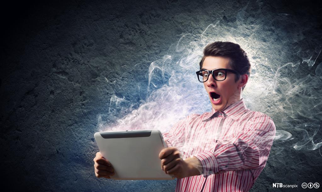 Ung mann ser sjokkert på tablet-pc. Foto.