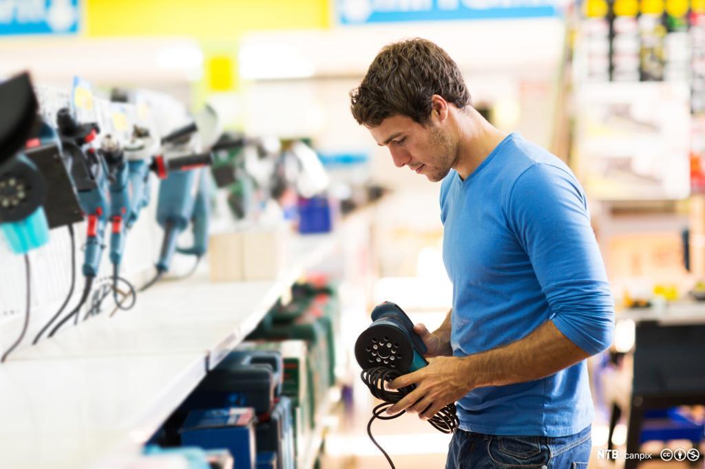 Ung mann som ser på pussemaskin i ein byggvarebutikk. Foto.