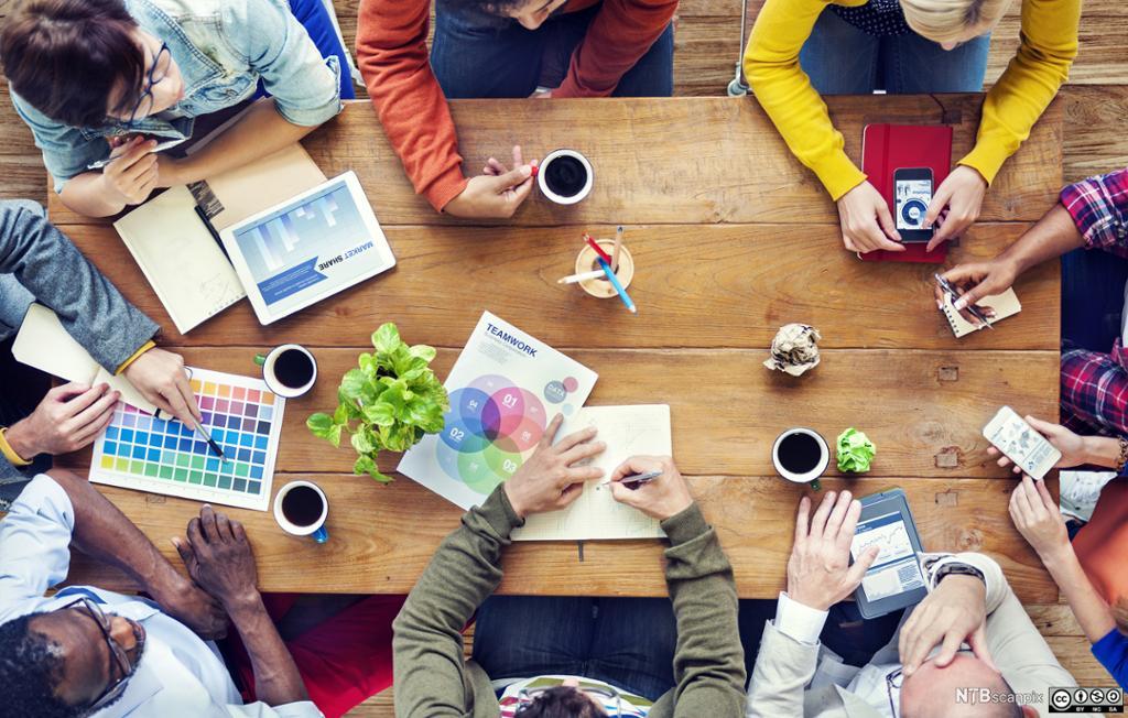 Personar samarbeider ved eit bord, sett frå fugleperspektiv. Foto.