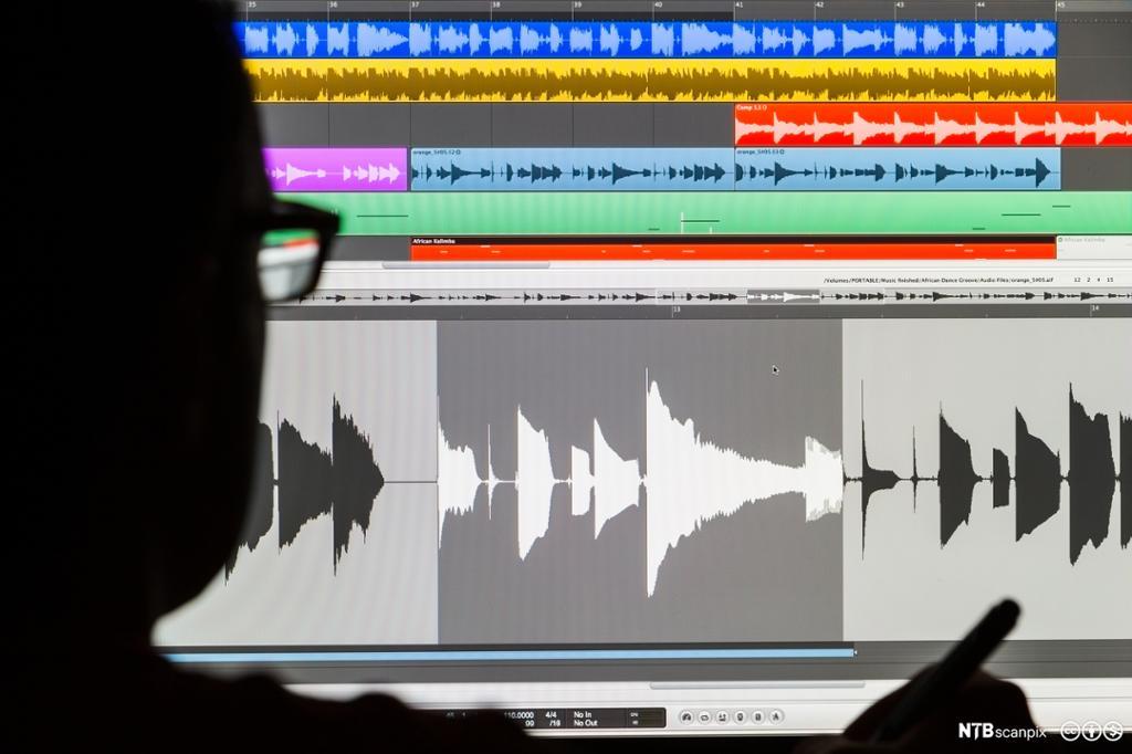 Silouhette av mann som redigerer lyd på en skjerm. Bilde.