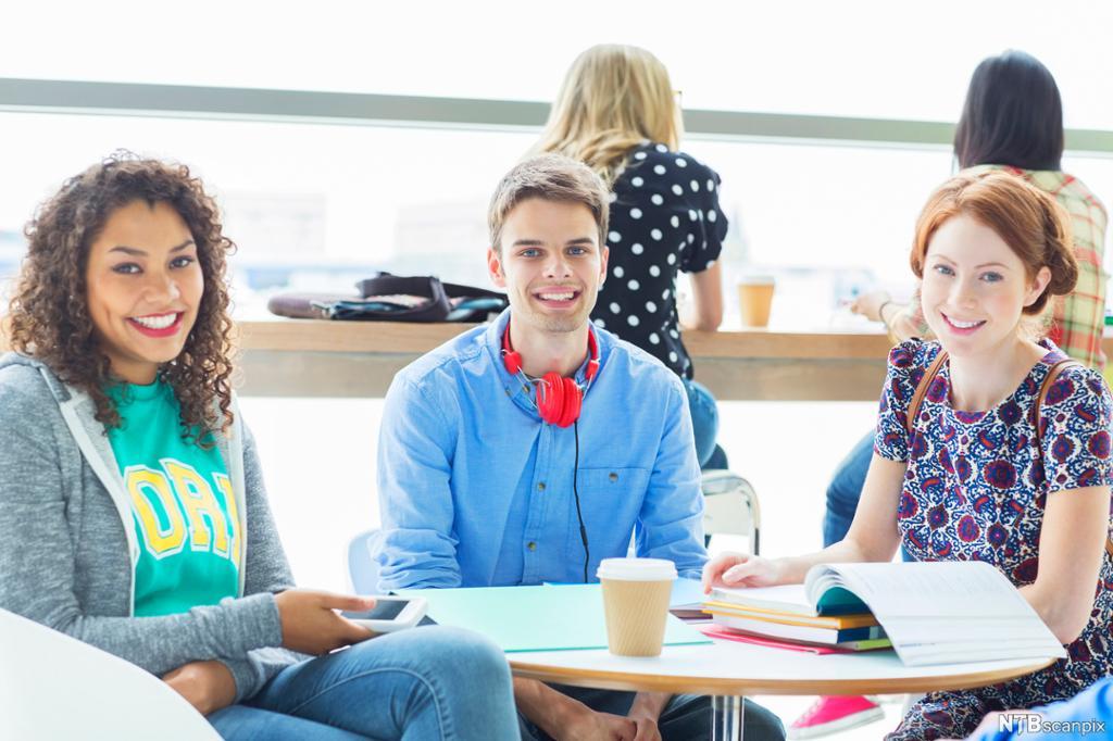 Tre unge mennesker sitter rundt et bord på en kafé og jobber med fag. På bordet er det ringpermer, skrivebøker og lesebøker. Foto.