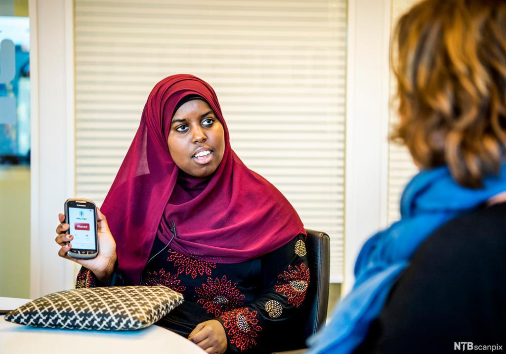 Mørkhudet kvinne med hidjab og mobiltelefon i samtale med en annen kvinne. Foto.